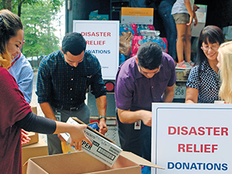 Volunteers packing boxes and loading a truck for disaster relief aid
