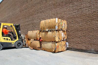 Worker moving recycling material with forklift